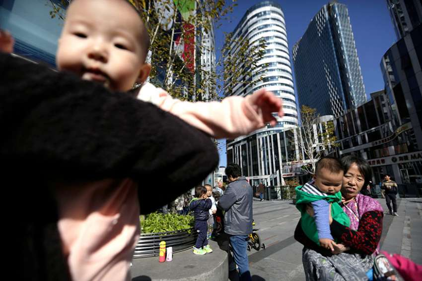 Women carry their babies in a shopping district in Beijing, China, in this Oct. 30, 2015, file photo.