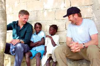 Mary's Meals founder Magnus MacFarlane-Barrow, left, is joined by actor Gerard Butler, right, with some of the children Mary's Meals supports through its program to alleviate poverty in 19 nations around the world.