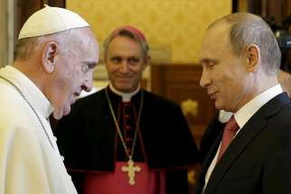 Pope Francis greets Russian President Vladimir Putin as he arrives for a private meeting at the Vatican June 10. At center is Archbishop Georg Ganswein, prefect of the papal household.