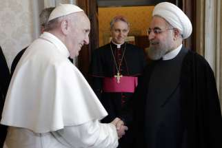 Pope Francis greets Iranian President Hassan Rouhani during a private meeting at the Vatican Jan. 26. Looking on is is Archbishop Georg Ganswein, prefect of the papal household.