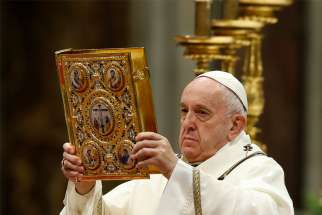 Pope Francis raises the Book of the Gospels as he celebrates Mass marking the feast of the Epiphany in St. Peter's Basilica at the Vatican Jan. 6, 2020.