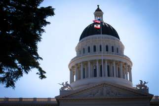 U.S. and California flags fly in front of the dome of the California Capitol in Sacramento May 9, 2019.