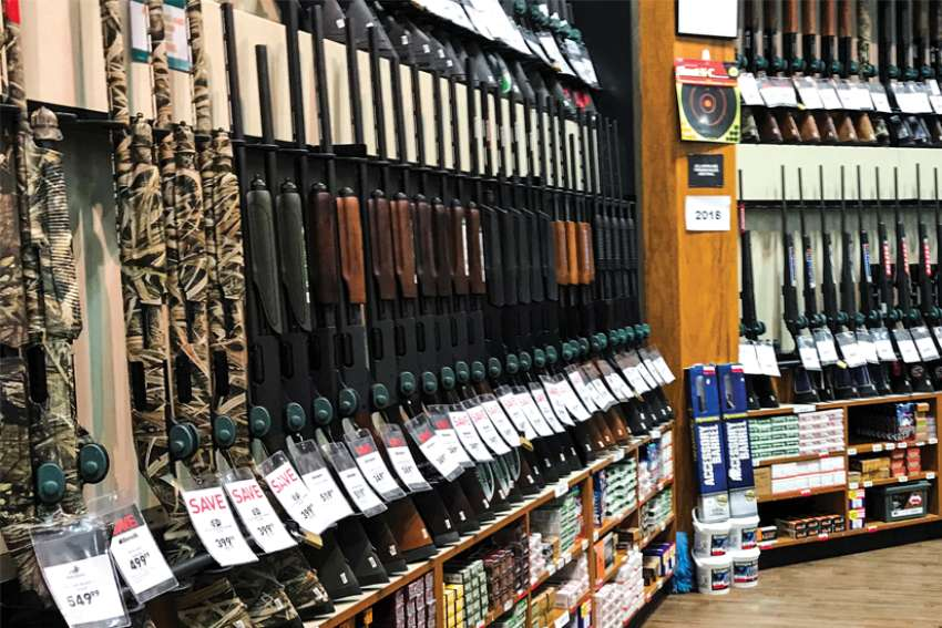 Rifles are seen inside the gun section of an American sporting goods store.
