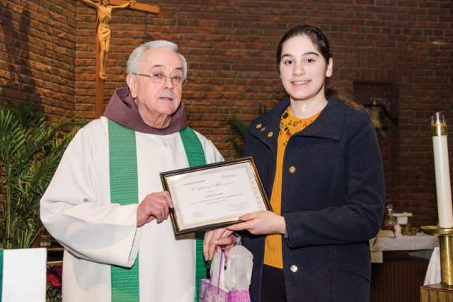 Fr. Damian MacPherson of the Franciscan Friars of the Atonement-Graymoor presents Raquel Seara with the second-place certificate from the annual essay contest for the Week of Prayer for Christian Unity.