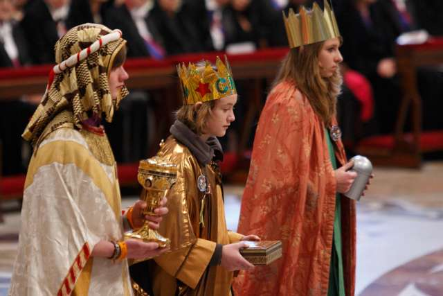 Three young people from Korschenbroich, Germany, dressed as the Magi, carry the offertory gifts during Mass on the feast of Mary Mother of God in St. Peter's Basilica at the Vatican Jan. 1.