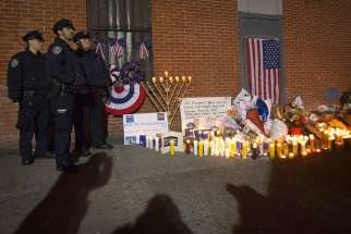 olice officers stand solemnly by a makeshift memorial solemn during a late night vigil Dec. 22 at the site where two police officers were shot in the head in the Brooklyn borough of New York. An armed man walked up to two New York Police Department offi cers sitting inside a patrol car and opened fire Dec. 20, shooting both of them fatally before running into a nearby subway station and committing suicide, police said.
