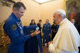 Pope Francis accepts a gift of a flight suit from Italian astronaut Paolo A. Nespoli during a meeting with astronauts from Expedition 53 of the International Space Station at the Vatican June 8. In October the pope spoke via a live link to the astronauts on the space station.