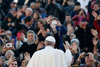 Pope Francis waves as he arrives to lead his weekly audience in St. Peter's Square at the Vatican Dec. 2