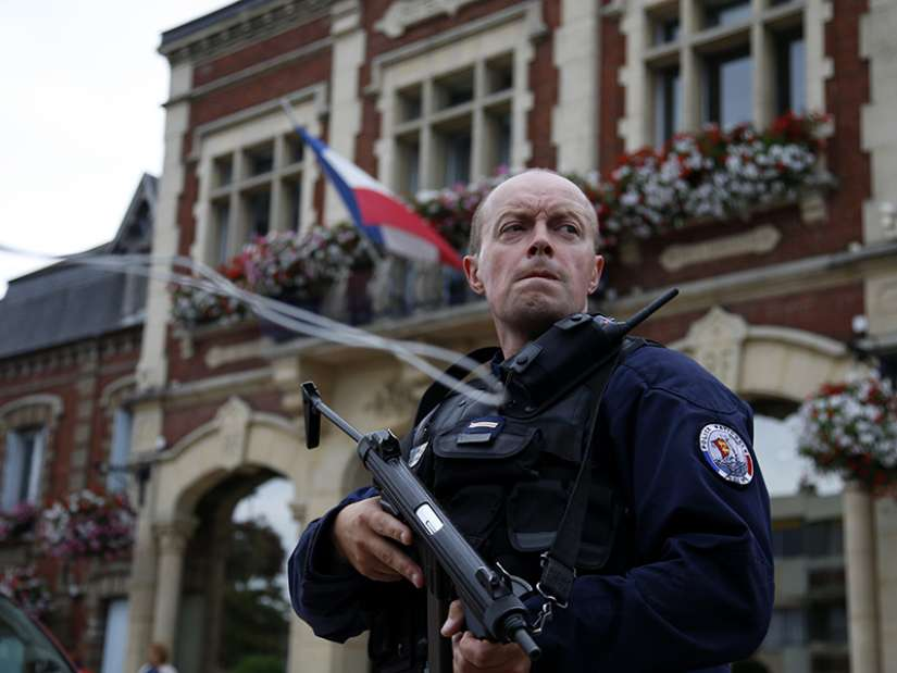 A policeman secures a position in front of the city hall after two assailants took five people hostage in the church at Saint-Etienne-du-Rouvray near Rouen in Normandy, France, July 26, 2016. The attackers killed a priest and seriously wounded another hostage before being shot dead by police.