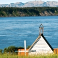 The Mackenzie River slips by the old Anglican church in Tulita with the Mackenzie Mountains in the background. The church built in 1880 is now an historic site and a testament to the 200-year Christian history of the Sahtu region in the Northwest Territories.