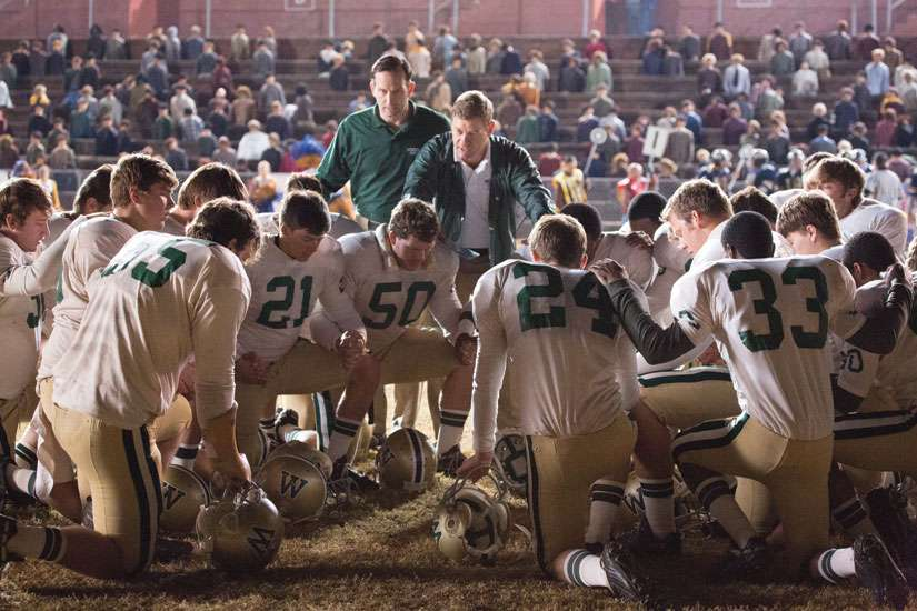 The Woodlawn High School football team, led by defensive co-ordinator Jerry Stearsn (Kevin Sizemore), top left, and head coach Tandy Geralds (Nic Bishop), pause to pray before an important game.