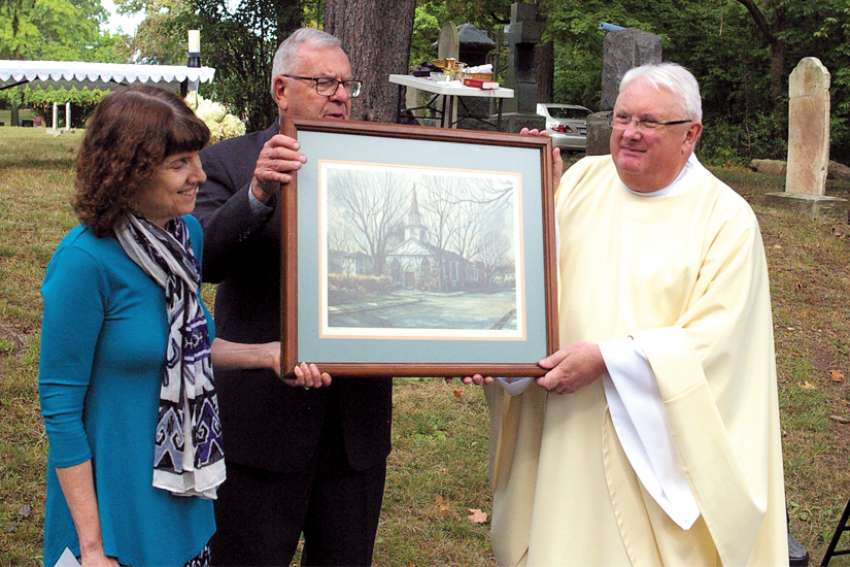 At the anniversary Mass held Sept. 15 at St. Mary's Cemetery, Fr. Cornelius (Con) O'Mahony, pastor at St. Andrew's, is presented with a limited edition historical print of the church done by Oakville artist Michael Hitchcox. Kevin Gleeson and Terry Murphy make the presentation.