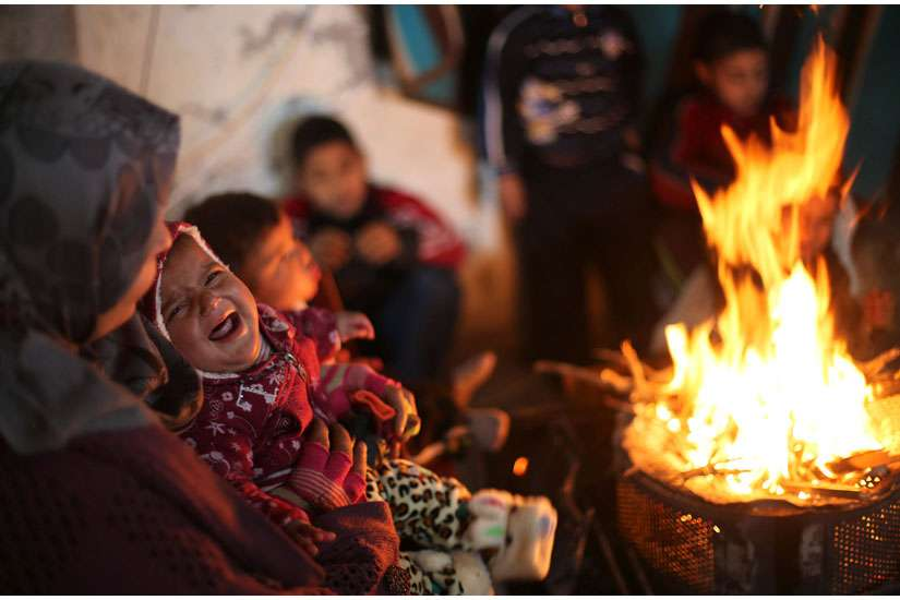 "A baby cries as members of a Palestinian family warm themselves by a fire Feb. 20 at the remains of their house that witnesses said was destroyed by Israeli shelling during a 50-day war last summer near Gaza City. Six months after the end of the most rec ent war in Gaza, one aid official said there is still a ""grave humanitarian crisis."""