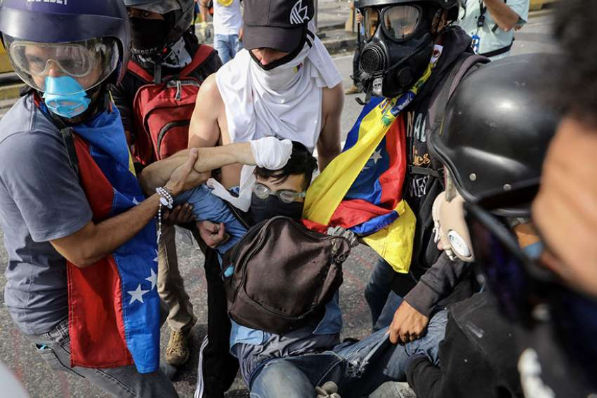 A group of demonstrators tries to help a man after he was shot by a Venezuelan military police sergeant June 22. On July 16, a armed civilians who support the Venezuela government opened fired against a large crowd. One person died from gunshot wounds and several others were injured.