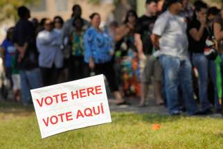 A sign in English and Spanish is seen as people wait to vote in 2012 outside a polling place in Kissimmee, Fla. A Pew Research Center poll released Oct. 10 shows Hispanic Americans give nearly a 5-1 edge to Democrats over Republicans as the party they feel is more concerned for them.