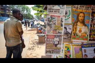 Men in Accra, Ghana, look at a newspaper stand in this Dec. 8, 2012, file photo. West African bishops urge Catholics to defend traditional marriage as influences from other nations are offered as keys to development.
