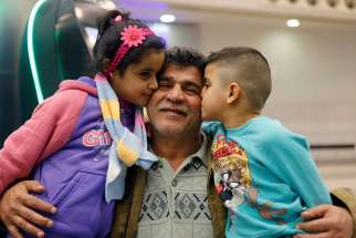 Nizar al-Qassab, an Iraqi Christian refugee from Mosul, gets a kiss from his children as they prepare to depart from Beirut international airport Feb. 8 en route to the United States. A three-panel federal appeals court upheld a temporary restraining order against President Donald Trump's refugee and travel ban.