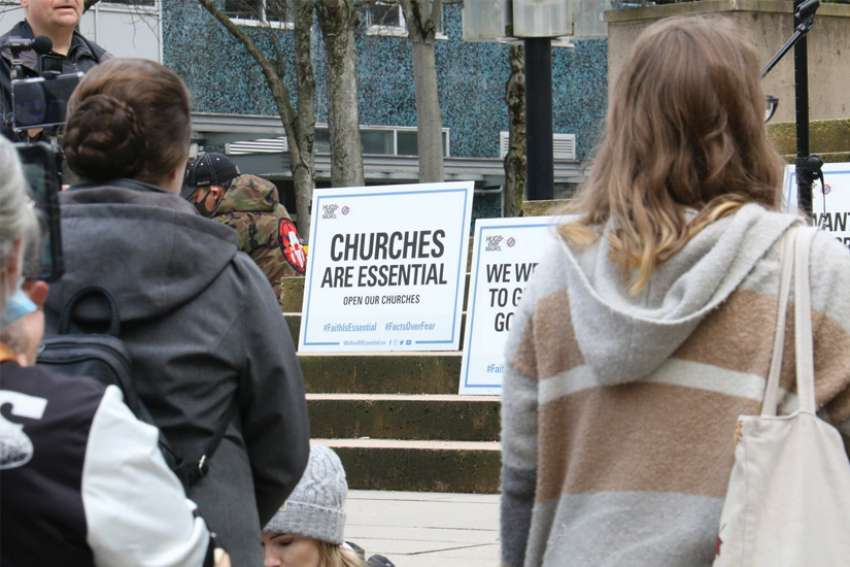 Protesters outside the B.C. Supreme Court with signs demanding church services be allowed.