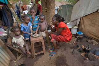 A mother and her children eat a meal at a camp for internally displaced persons on the grounds of St. Mary Catholic Cathedral April 24 in Wau, South Sudan. Drought and armed conflict have pushed tens of thousands of Wau-area residents out of their homes, away from their farms and unable to adequately feed themselves.