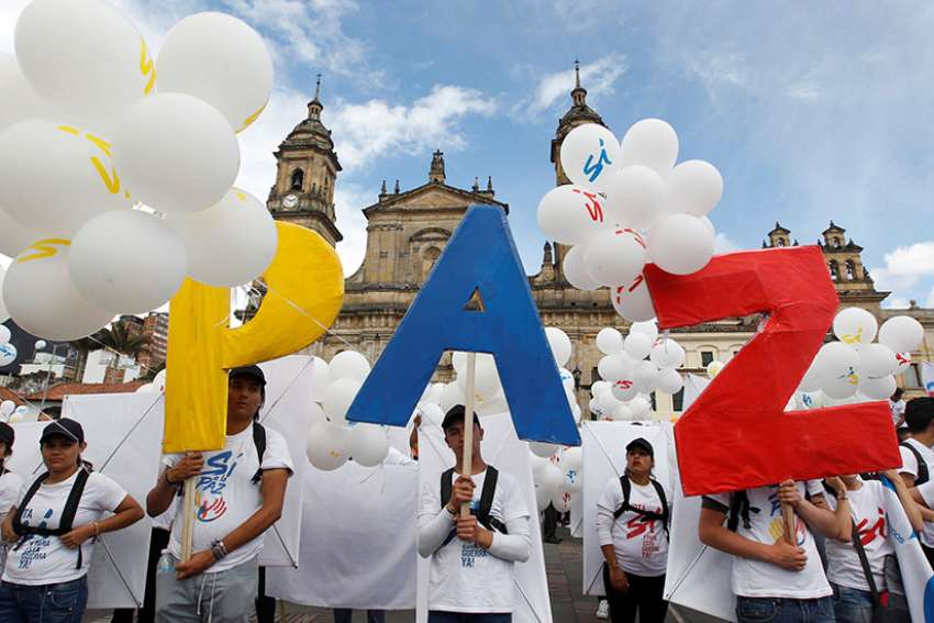 "People form the word peace outside the cathedral in Bogota, Colombia, Sept. 26, 2016. To chants of ""No more war,"" the Colombian government and Marxist rebels signed an agreement that day to end Latin America's last armed conflict."