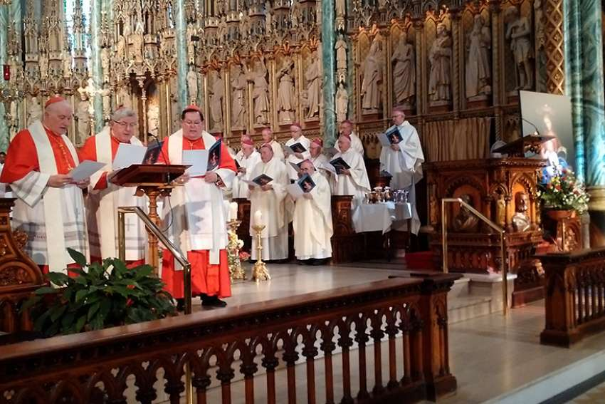 Cardinals (from left) Marc Ouellet, Thomas Collins and Gerald Lacroix read the prayer of consecration on Sept. 27 at Notre Dame Cathedral in Ottawa.