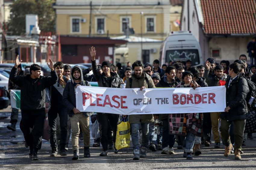 Refugees and migrants hold a banner and shout slogans Nov. 11 as they walk toward the Croatian border in Belgrade, Serbia. English Cardinal Vincent Nichols said some British media stirred up xenophobic sentiments against migrants and refugees.