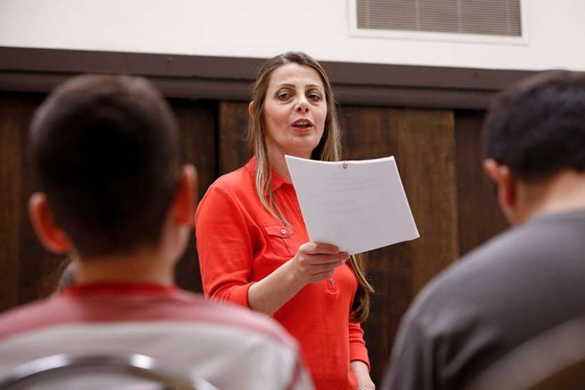 Maureen Antwan practices with the Holy Family Mission children's choir at a church in Phoenix March 25. Her family fled Iraq in 2004 out of fear of war and persecution.