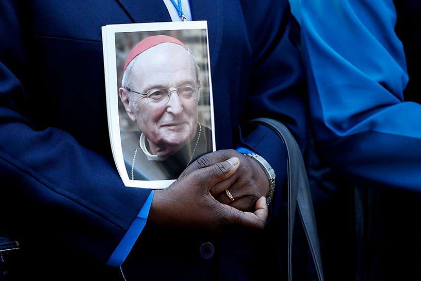 A mourner holds a portrait of Cardinal Joachim Meisner of Cologne, Germany, prior to his funeral July 15.