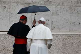 Pope Francis and Cardinal Oscar Rodriguez Maradiaga of Tegucigalpa, Honduras, share an umbrella as they leave a session of the Synod of Bishops on young people, the faith and vocational discernment at the Vatican Oct. 11.
