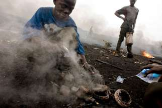 In this Aug. 8, 2008, file photo, a boy salvages copper found inside a burned motor in Accra, Ghana