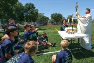 Fr. Michael Daly holds a monstrance with the Eucharist during Faith and Football Camp at Cretin-Derham Hall High School in St. Paul, Minn. The three-day camp featured football drills and scrimmages mixed in with Mass, rosary, Stations of the Cross and adoration.