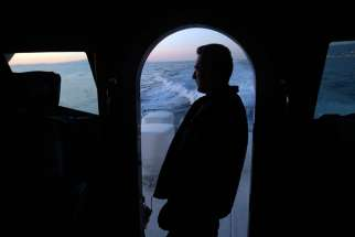 A sailor from the Greek Coast Guard monitors the Mediterranean Sea for undocumented migrants Sept. 24, 2014