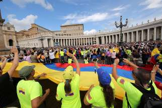 Pilgrims hold a large Colombian flag as Pope Francis leads the Angelus in St. Peter's Square Sept. 17 at the Vatican.