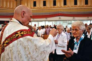 Saskatoon Bishop Mark Hagemoen gives communion to Sr. Brigitta Haag, the oldest of the Ursuline order in Saskatchewan at 100 years old, during a Mass to mark the centennial of the order's arrival in the province.