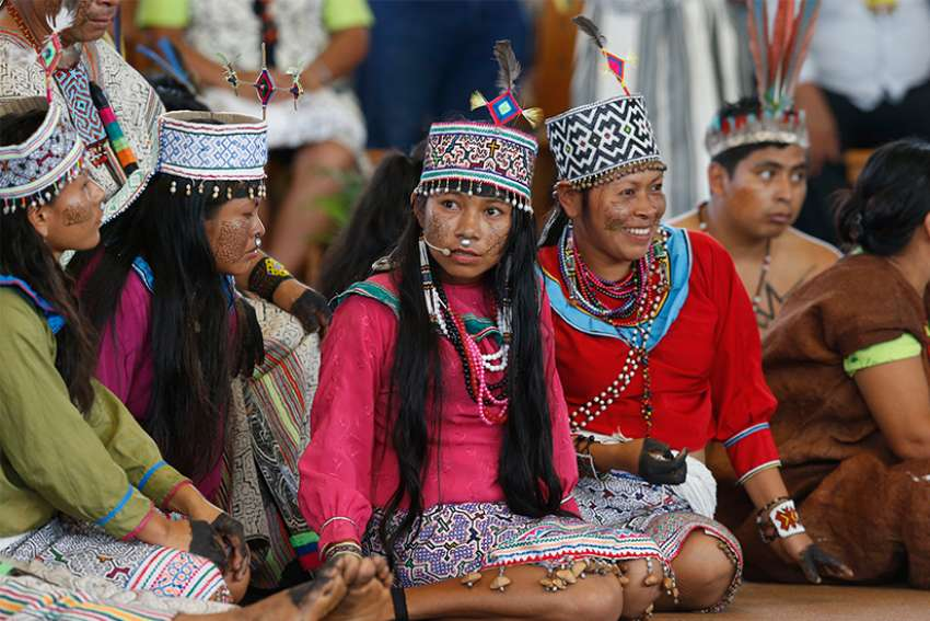 Young members of an indigenous group from the Amazon region listen during a meeting with Pope Francis Jan. 19 at Madre de Dios stadium in Puerto Maldonado, Peru.