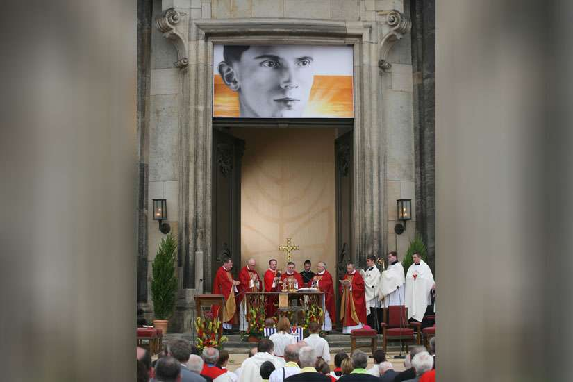 "An image of Father Alois Andritzki hangs above the altar during his Mass of beatification in Dresden, Germany, June 13, 2011. The young German priest was executed in 1943 at the Nazi death camp of Dachau. In his sermon, Bishop Joachim Reinelt of Dresden-Meisse n praised Blessed Andritzki, saying he had shown a ""bright face"" while enduring the ""most awful beastly work"" at the concentration camp. ("