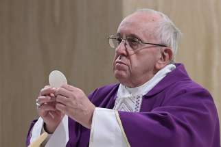 Pope Francis elevates the Eucharist as he celebrates morning Mass in the chapel of the Domus Sanctae Marthae at the Vatican March 12. In his homily, the pope said true Christians take risks to constantly seek out Christ.