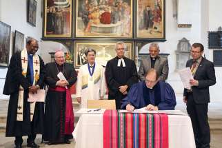 Reformed, Catholic, Lutheran and Methodist leaders look on in St. Mary's City Church in Wittenberg, Germany, as the Rev. Chris Ferguson, World Communion of Reformed Churches general secretary, signs the declaration expressing Reformed churches' support for the Catholic-Lutheran Joint Declaration on the Doctrine of Justification.