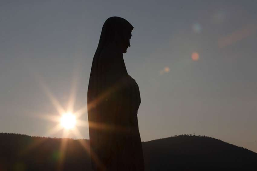 The sun sets behind a statue of Mary on Apparition Hill in Medjugorje, Bosnia-Herzegovina, in this 2011 file photo.