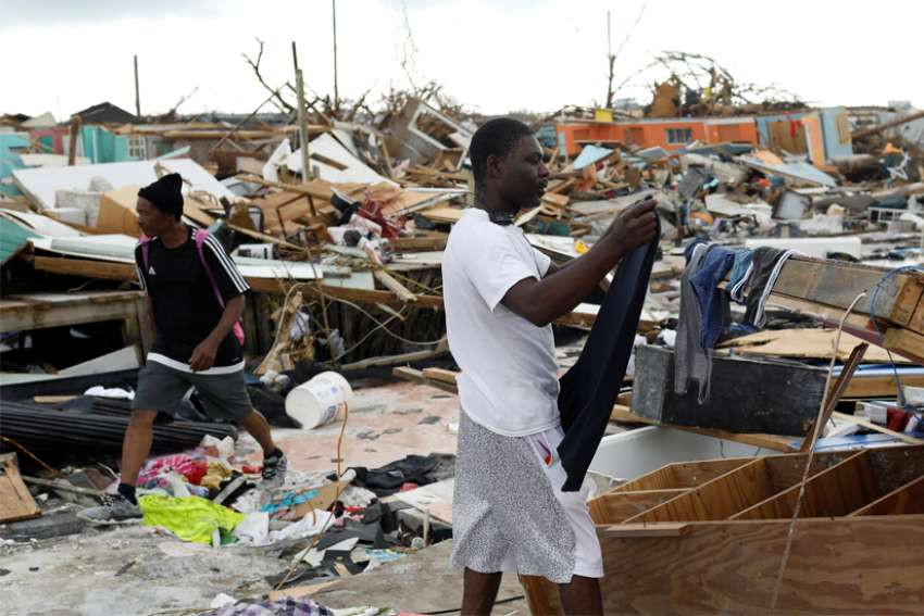 A man hangs his clothing amid the rubble of destroyed homes Sept. 6, 2019, after Hurricane Dorian hit the Abaco Islands in Marsh Harbour, Bahamas. In the wake of Hurricane Dorian's brutal blasting of the Bahamas, Catholic organizations in Florida continued to raise funds to aid victims there.