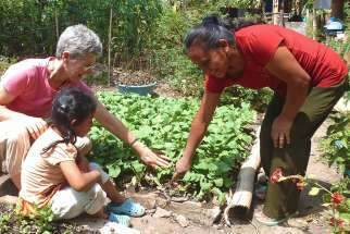 Maryknoll Lay Missioner Peg Vamosy, who has been with the organization since 2008 and served in three countries, is seen with a woman and child at a garden in El Salvador.