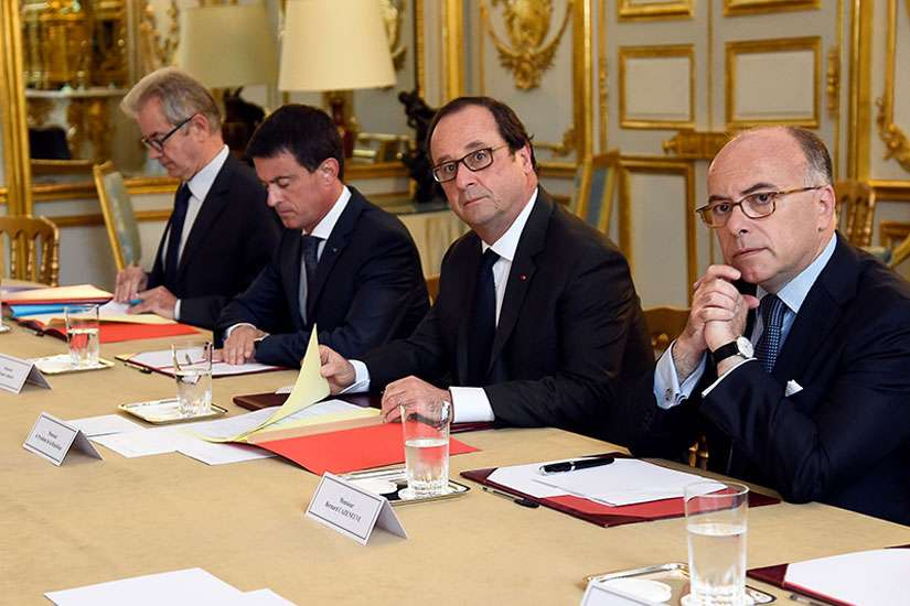 French Prime Minister Manuel Valls, second from left; President Francois Hollande, third from left; and Interior Minister Bernard Cazeneuve, right, look on during a meeting with French representatives of religious communities at the Elysee Palace in Paris on July 27, 2016.