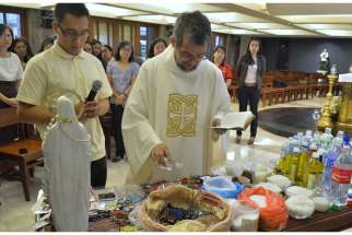"Msgr. Jesus-Norriel Bandojo, a priest in the the Office of Exorcism of the Manila Archdiocese in the Philippines, gives a blessing and says a prayer of deliverance over ""sacramentals"" in late October at the archdiocese offices' chapel to ward off the pos sibility of evil forces attaching themselves to the religious items."