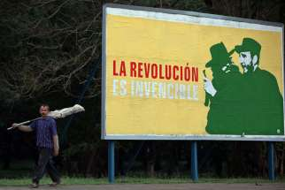 "A man walks past a Cuban revolutionary billboard in Havana Dec. 26, 2014, reading ""The Revolution is Invincible."" Pope Francis played a key role in restoring U.S.-Cuban diplomatic ties."