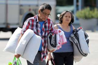 Evacuees from the Fort McMurray wildfire leave The Expo Center May 4 after receiving bedding supplies in Edmonton, Alberta. The entire population of Fort McMurray has been evacuated because of the wildfire.