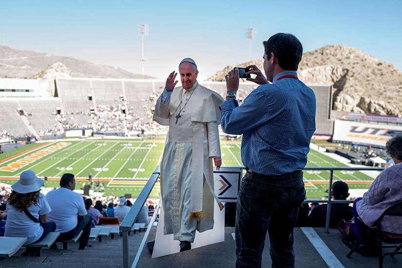 A man takes a photo of a life-size cutout of Pope Francis at the Sun Bowl in El Paso, Texas, Feb. 17. Thousands filled the stadium to watch Pope Francis celebrate Mass in nearby Ciudad Juarez, Mexico. It was simulcast on the stadium's big screen.