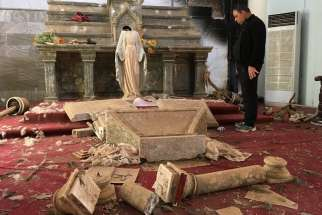 A Catholic church destroyed by Islamic State militants in Karamdes, Iraq, is examined by a priest March 6, 2018. The genocide conducted by the Islamic State against Christian communities in Iraq and Syria has turned into continued harassment by Iran-backed militias and shows no signs of abating soon, said speakers at a Sept. 26, 2019, hearing in Washington.