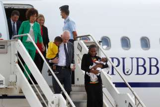 Meriam Ibrahim of Sudan carries one of her children as she arrives with Lapo Pistelli, Italy's vice minister for foreign affairs, holding her other child, Italy's Prime Minister Matteo Renzi, left, and his wife Agnese, second from left in green, after landing at a Rome airport July 24. The Sudanese woman, who was spared a death sentence for converting from Islam to Christianity and then was barred from leaving Sudan, left Italy on July 31 on a flight for the United States where she plans to build a new life.