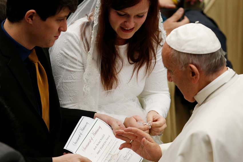 Pope Francis blesses the marriage certificate of a U.S. couple during his general audience in Paul VI hall at the Vatican Dec. 14, 2016.