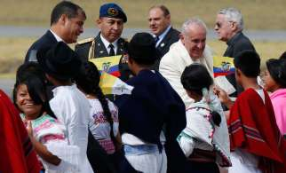 Pope Francis greets children in traditional dress as he arrives at Mariscal Sucre International Airport in Quito, Ecuador, July 5. Also pictured is Ecuadorean President Rafael Correa, left. The Pope is making an eight-day trip to Ecuador, Bolivia and Paraguay.